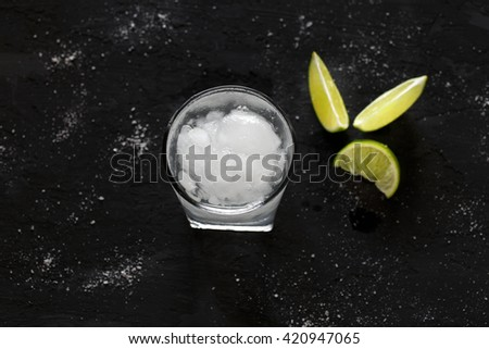 Cocktail vodka or gin with ice and lime on a dark background, top view with copy space - stock photo