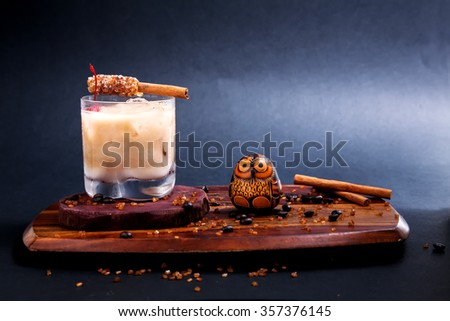 Cocktail/White russian with sugar cinnamon stick on wooden in Black background. - stock photo