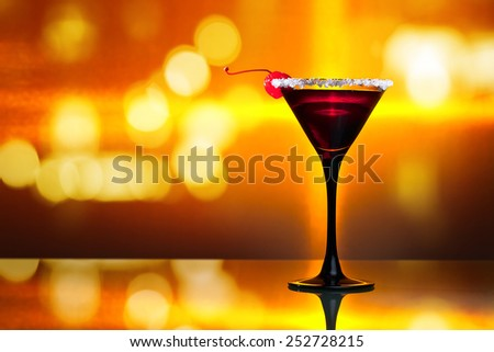 cocktail with cherry on glass table in bar - stock photo