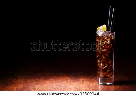 Cocktail with cola on a wooden table - stock photo