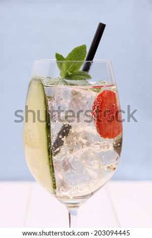 Cocktail with cucumber, strawberry in wine glass, close up