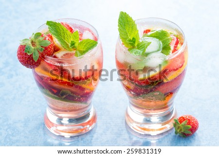 cocktail with fresh strawberries and citrus in glasses, close-up - stock photo