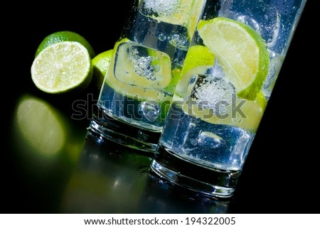 Cocktail with ice and lime slice on black table, disco club atmosphere - stock photo