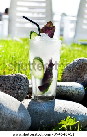 cocktail with ice crumbs, cucumber and basil