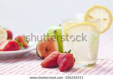 cocktail with ice,lemon, fig and strawberries on a plate - stock photo