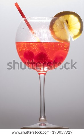 Cocktail with lemon slice, cherry and a straw - stock photo