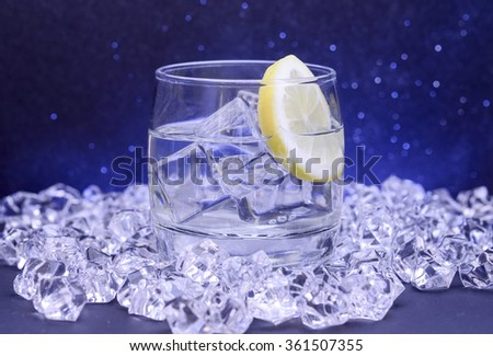 Cocktail with lemon slice surrounded by ice - stock photo