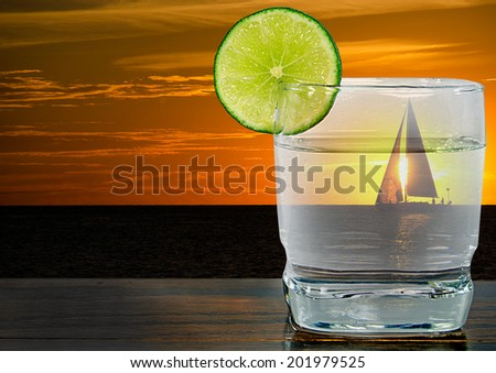 cocktail with lime garnish and sunset with sailboat background. - stock photo