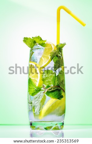 Cocktail with mint and lemon on the bar on the green background. - stock photo