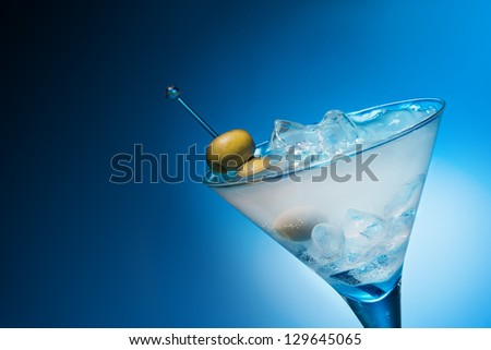 Cocktail with olives on blue background - stock photo