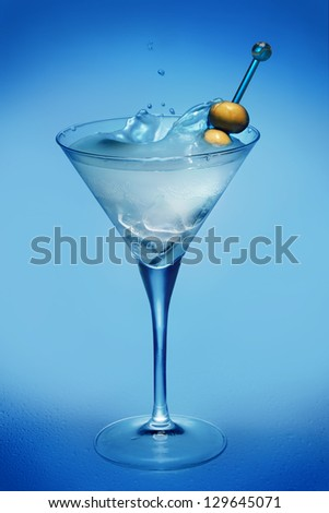 Cocktail with olives on blue background
