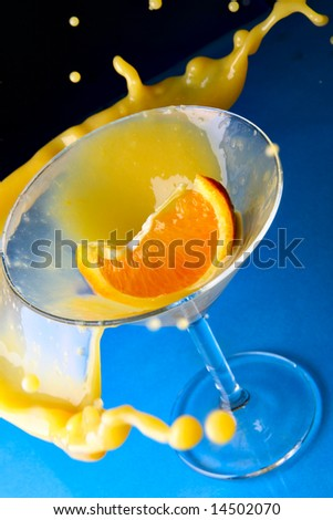 Cocktail with orange in glass with splashes close-up over blue background - stock photo