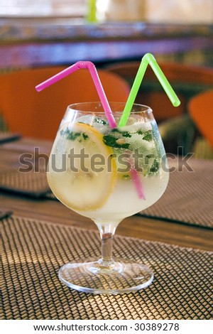 cocktail with two straws on the table in cafe - stock photo