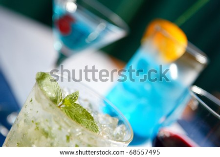 Cocktails and different drinks stand one after another different colors - stock photo