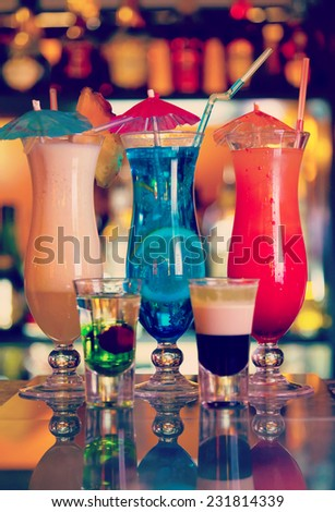 Cocktails Blue Lagoon, Pina Colada and Sunrise with illuminated bar on the background - stock photo