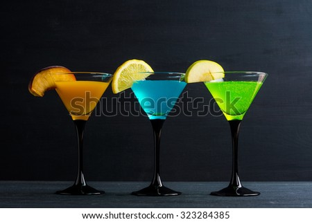 Cocktails garnished with fruits on the black wooden background