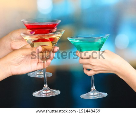 Cocktails in hands in nightclub - stock photo