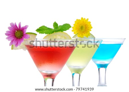 Cocktails martini row with vodka, light rum, gin, tequila, blue curacao, lime juice, lemonade, lemon slice and fresh summer flowers in martinis cocktail glass on a white background - stock photo