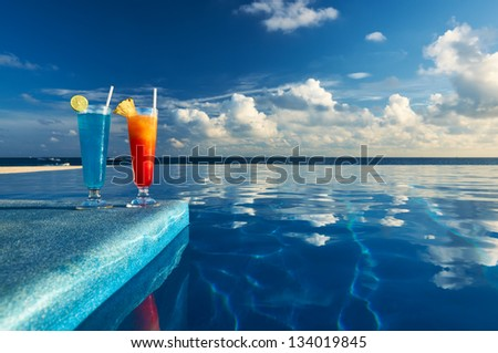 Cocktails near the swimming pool - stock photo