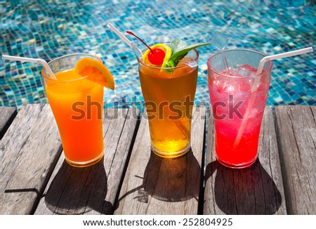 Cocktails near the swimming pool on the background of the water - stock photo