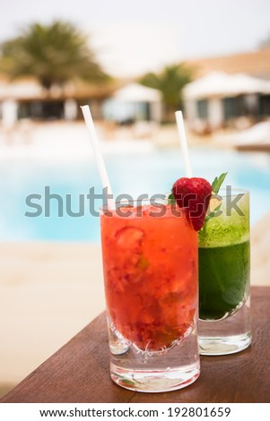 Cocktails near the swimming pool red and green - stock photo