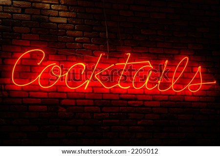 Cocktails neon sign illuminated against a brick wall at night - stock photo