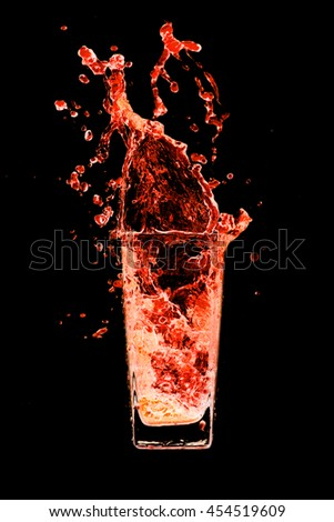 Cocktails orange splash out of glass on a black background.  - stock photo