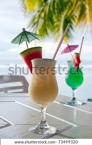 Cocktails; Pina Colada and Maitai on an island resort with the lagoon & coconut palm tree behind - stock photo
