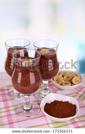 Cocktails with banana and chocolate on table on light background - stock photo