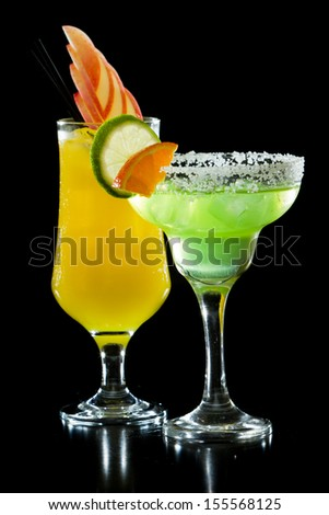 cocktails with bright colors isolated on a black background garnished with fresh fruit