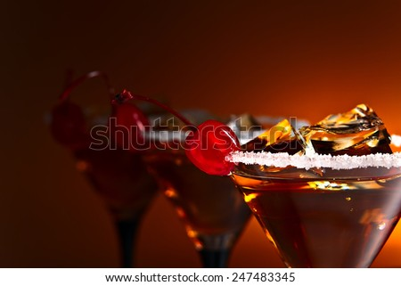 cocktails with cherry and ice , focus on foreground - stock photo