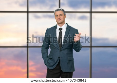 Cocky adult businessman wearing suit. Proud man on sunrise background. I'd like to know more. We need to talk. - stock photo