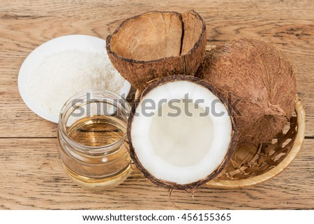 Coco oil and chips next to a basket with coconuts on an old wooden table - stock photo