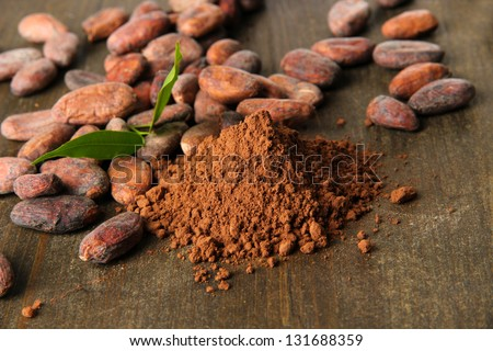 Cocoa beans and cocoa powder on wooden background - stock photo
