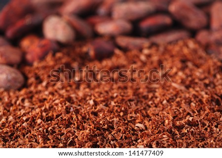 cocoa beans and grated chocolate background,  shallow dof - stock photo