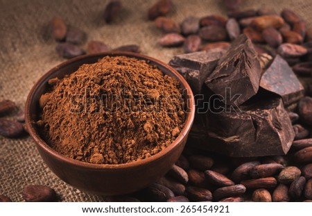 Cocoa beans, clay bowl with cocoa powder, black chocolate on brown sacking - stock photo
