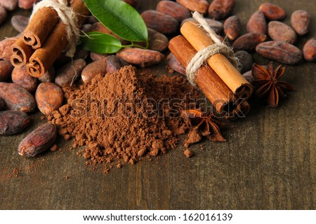 Cocoa beans, cocoa powder and spices on wooden background - stock photo