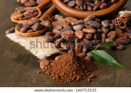 Cocoa beans in bowl, cocoa powder and spices on wooden background - stock photo