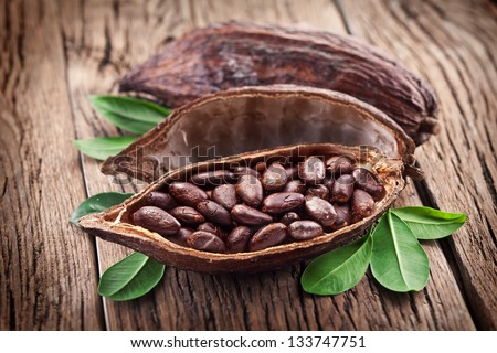 Cocoa pod with cocoa beans on a dark wooden table.
