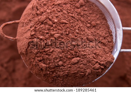 Cocoa powder, a stainless steel mesh - stock photo
