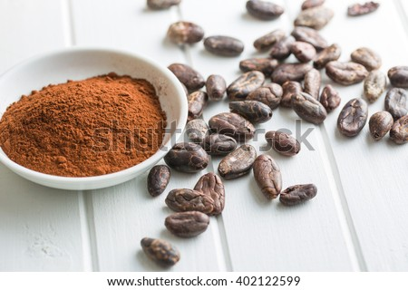 cocoa powder and beans on kitchen table - stock photo
