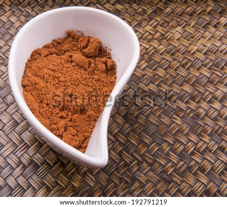 Cocoa powder for making drinks in a white ceramic container over wicker background - stock photo