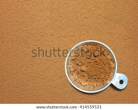 Cocoa powder in measuring cup on cocoa powder background