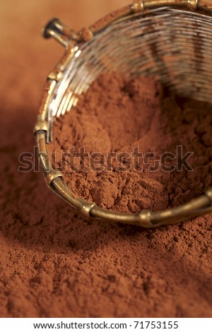 cocoa powder in old rustic style silver sieve, shallow dof