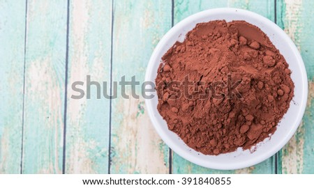 Cocoa powder in white bowl over wooden background - stock photo
