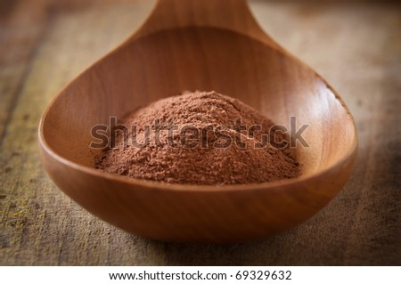 cocoa powder in wooden spoon - stock photo
