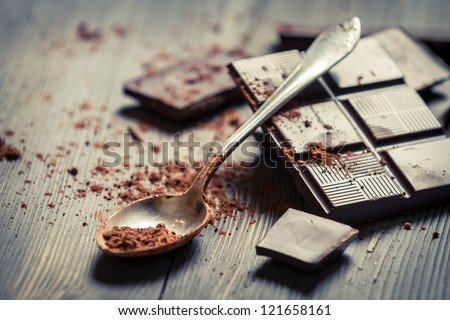Cocoa Powder on spoon and Dark Chocolate background - stock photo