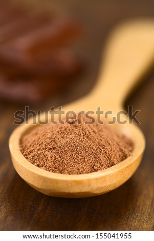 Cocoa powder on wooden spoon with chocolate pieces in the back (Very Shallow Depth of Field, Focus one third into the cocoa) - stock photo