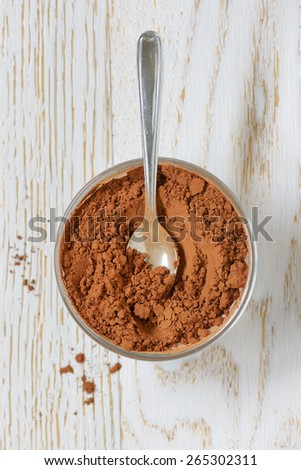 cocoa powder with spoon on wooden background - stock photo