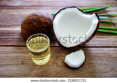 Coconut and coconut oil for alternative therapy on the wood table - stock photo